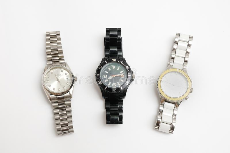Three metal strapped watches of silver, white and black color royalty free stock image