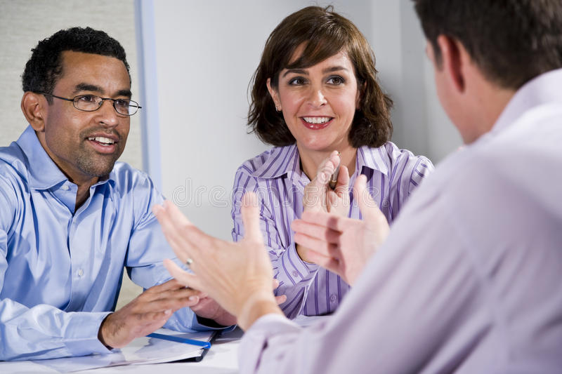 Three mid-adult people sitting at table meeting stock photos