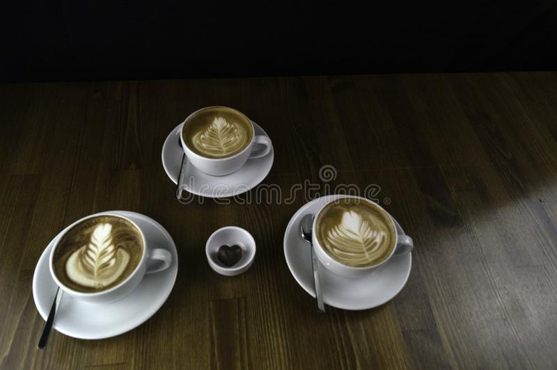 three cups ready to be served coffee with milk and chocolate royalty free stock photography