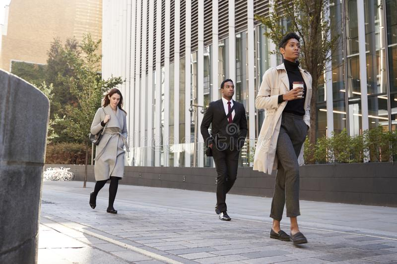 Three millennial city workers walking in the street, low angle, full length stock photos