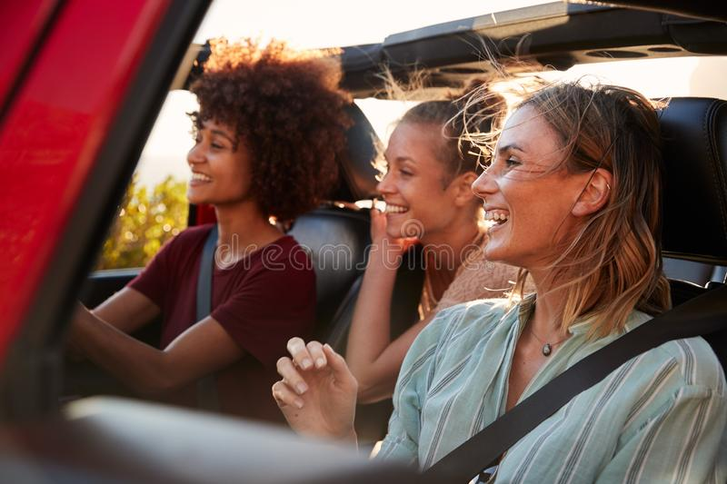 Three millennial female friends on a road trip driving together in an open jeep, close up royalty free stock photo