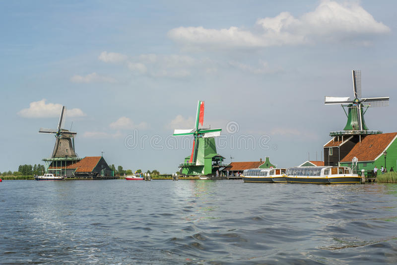 Three mills on the blue water with boats around in the day. In Zaanse Schans Netherlands stock photos