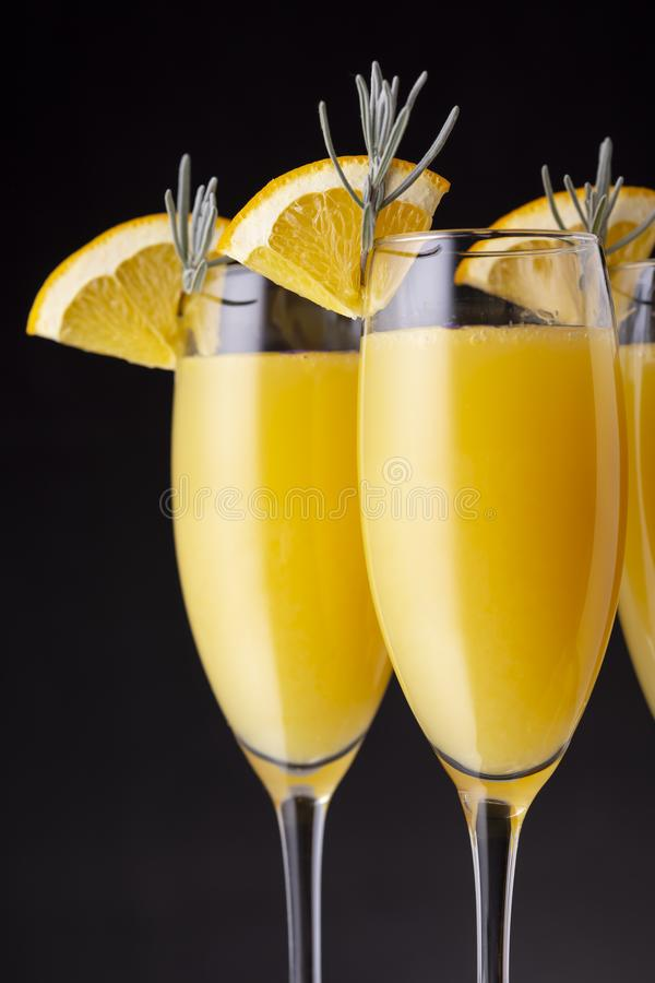 Three mimosa cocktails in champagne glasses. Detail of mimosa cocktails in champagne glasses with orange juice and sparkling wine decorated with lavender leaves royalty free stock photos