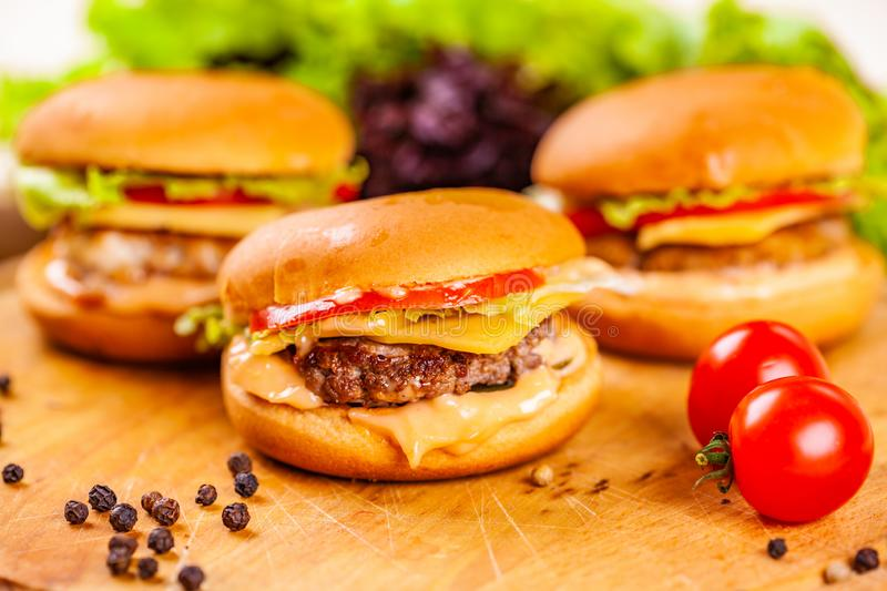 Three mini burgers with beef cutlets, tomatoes and cheese on wooden board. Close up royalty free stock photography
