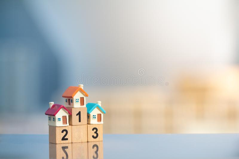 Three miniature houses on first place of winner podium on modern city background royalty free stock image