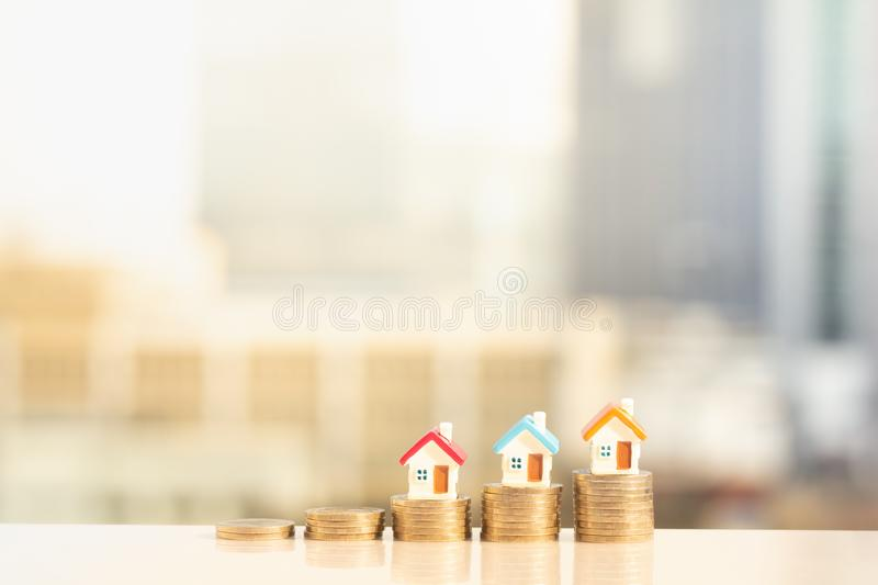 Three miniature houses on stack of coins on modern city background royalty free stock photo