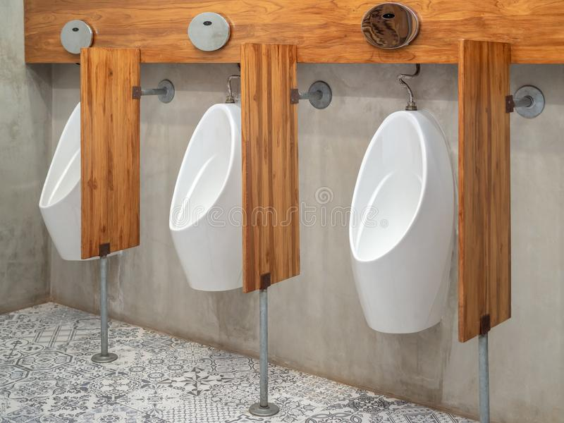 Three modern white automatic urinal for men and wood partitions on cement wall in toilet stock photography