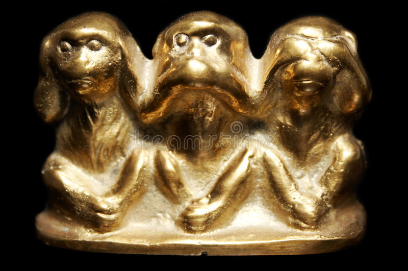 Three monkeys figurine. Three monkeys brass figurine on black background royalty free stock image
