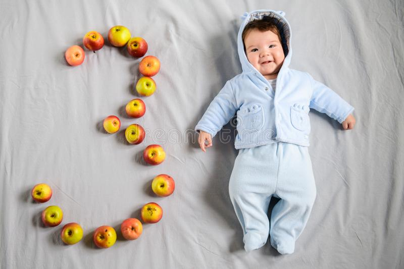 A three-month-old baby lies on a white sheet next to the handmade number of apples. Three month old baby concept. Top view, flat royalty free stock photos