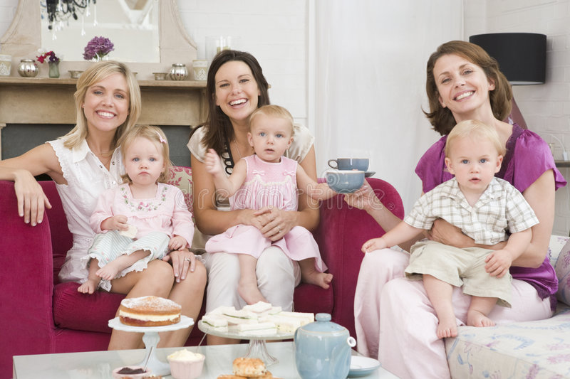 Three mothers in room with babies and coffee. Three mothers in living room with babies and coffee smiling stock photo