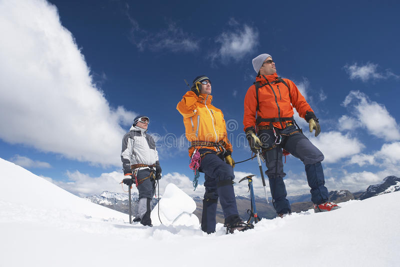 Three Mountain Climbers On Snowy Peak. Three male mountain climbers reaching snowy peak against clouds royalty free stock photography