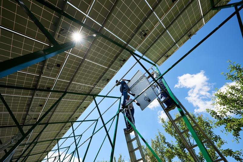 Three mounters holding solar panels on high metallic construction. royalty free stock images