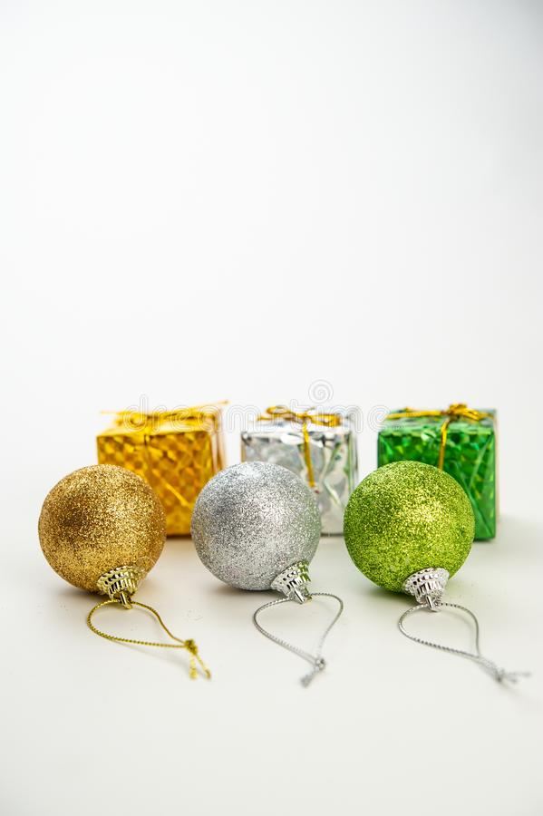 three multi-colored Christmas balls with golden ribbons and boxes with gifts on a light background. stock photos