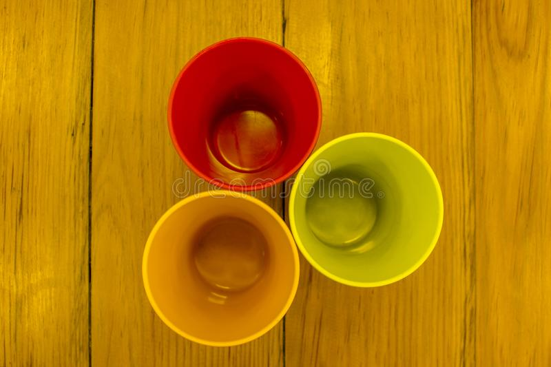 Three multi-colored glasses on a wooden table top view stock image