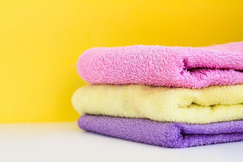 Three multi-colored Terry towels have a yellow wall on white background royalty free stock photos