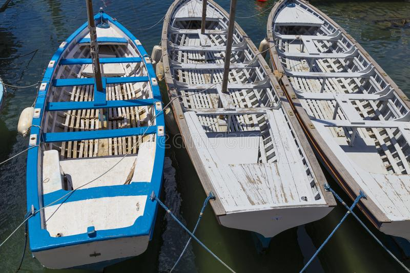Three multi-colored wooden boats on the water stock images