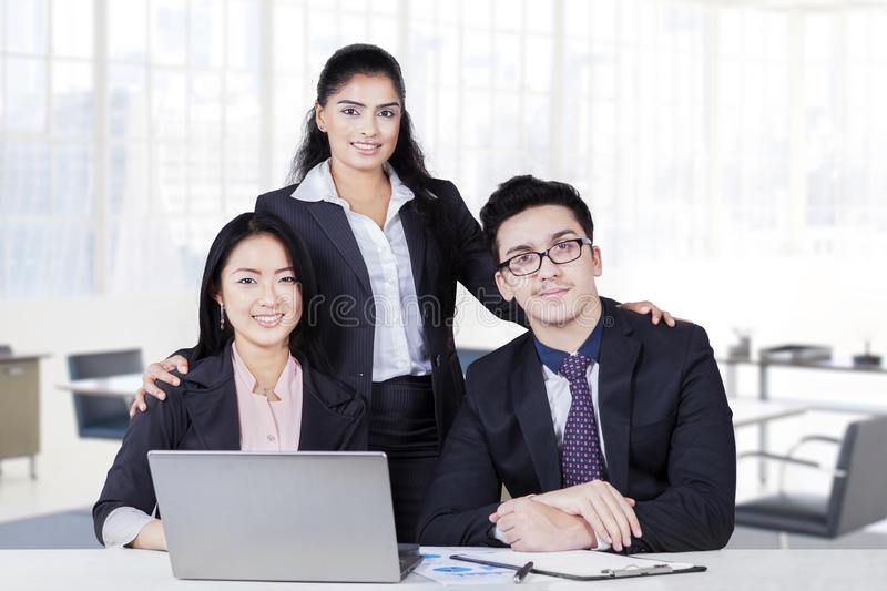 Three multi ethnic business team smiling in office stock image