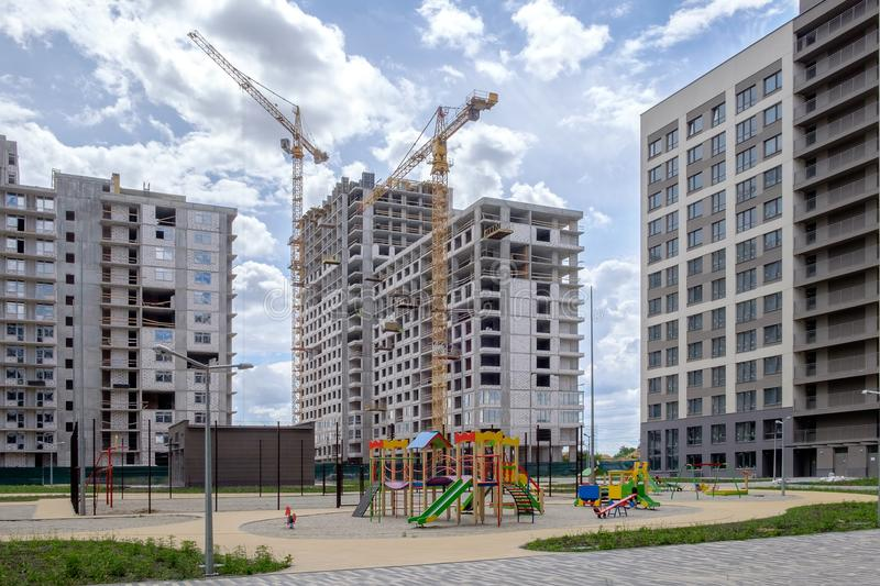 Three multi-storey houses, construction cranes, sports and children`s playground in the newly built area of Eastern Europe. The process of construction stock images