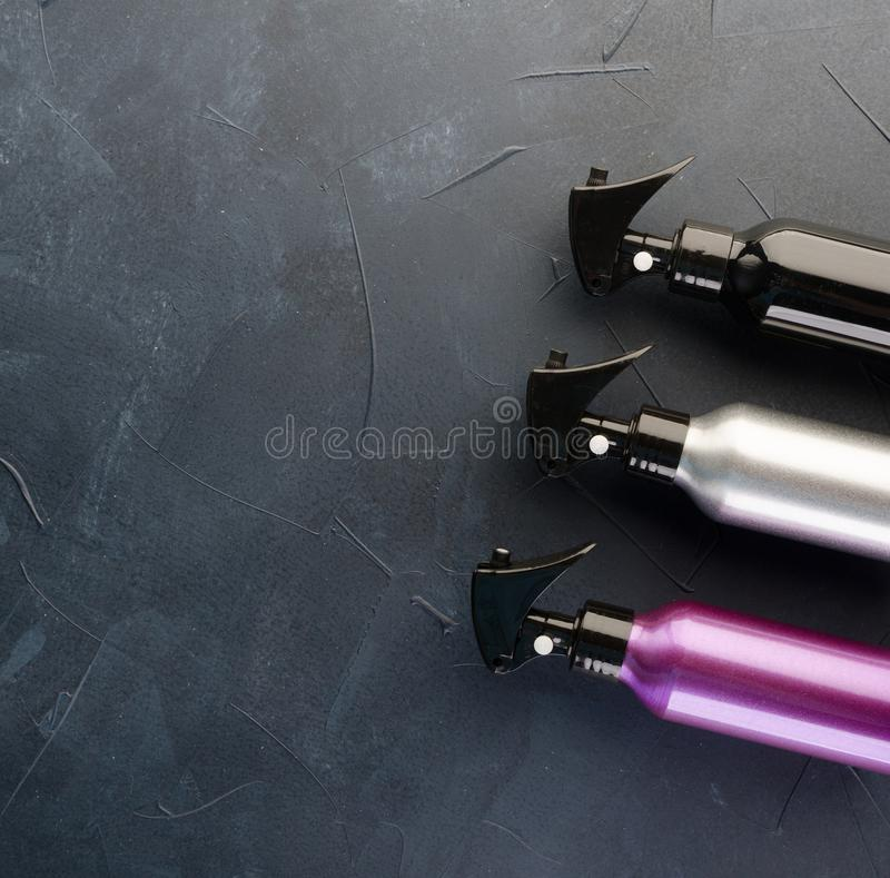 Three multicolored bottles of professional hair spray stock image