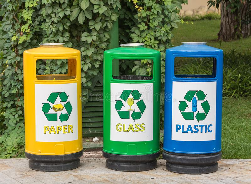 Three multicolored recycle bins for waste with icons for the convenience of sorting junk waste in the garden. Sunny summer day royalty free stock image