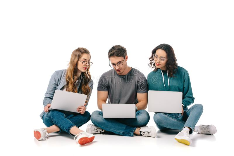 Three multicultural students sitting with laptops. On white royalty free stock photos