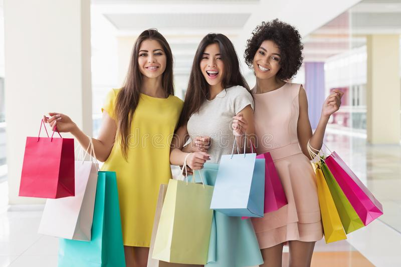 Three multiracial friends are happy after shopping stock photography