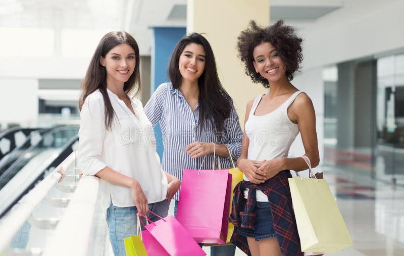 Three multiracial friends are happy after shopping in mall royalty free stock images