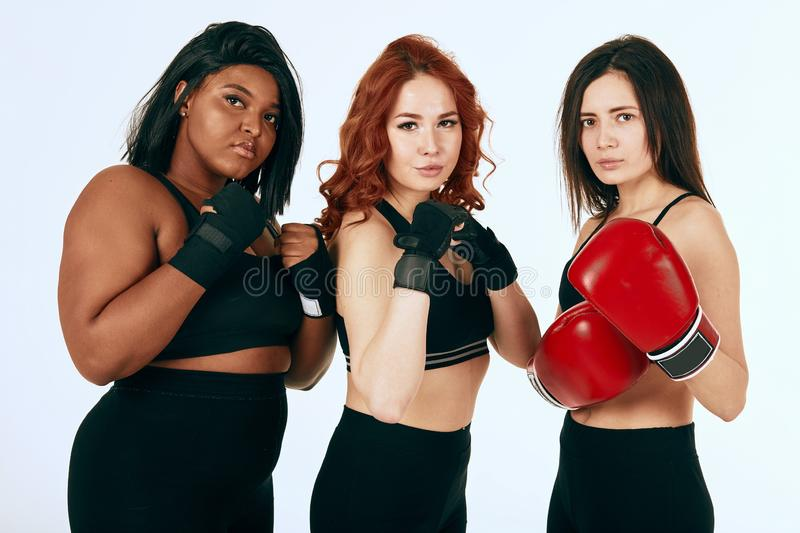 Three multiracial diverse woman in black sportswear posing in boxing gloves stock images