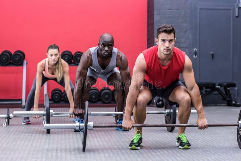 Three muscular athletes lifting barbells stock image