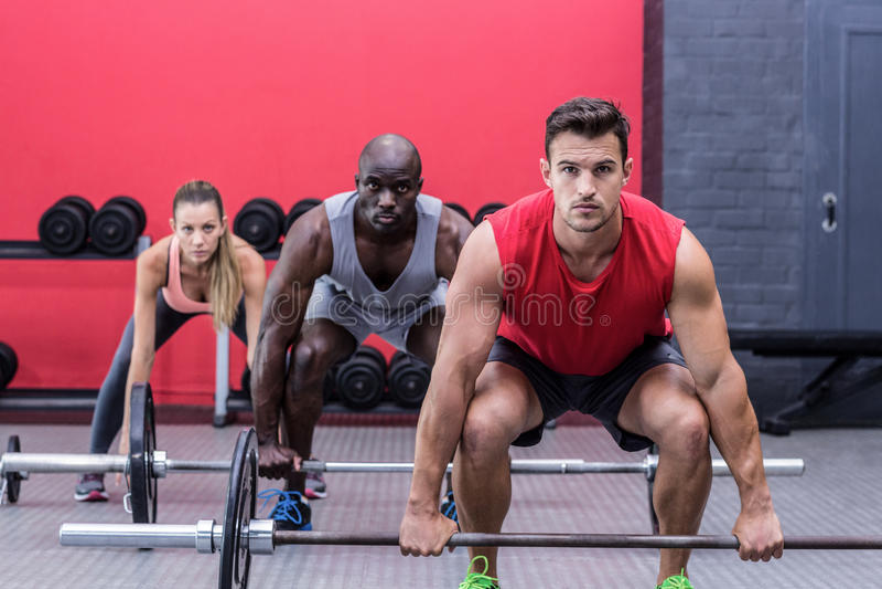 Three muscular athletes lifting barbells royalty free stock photos