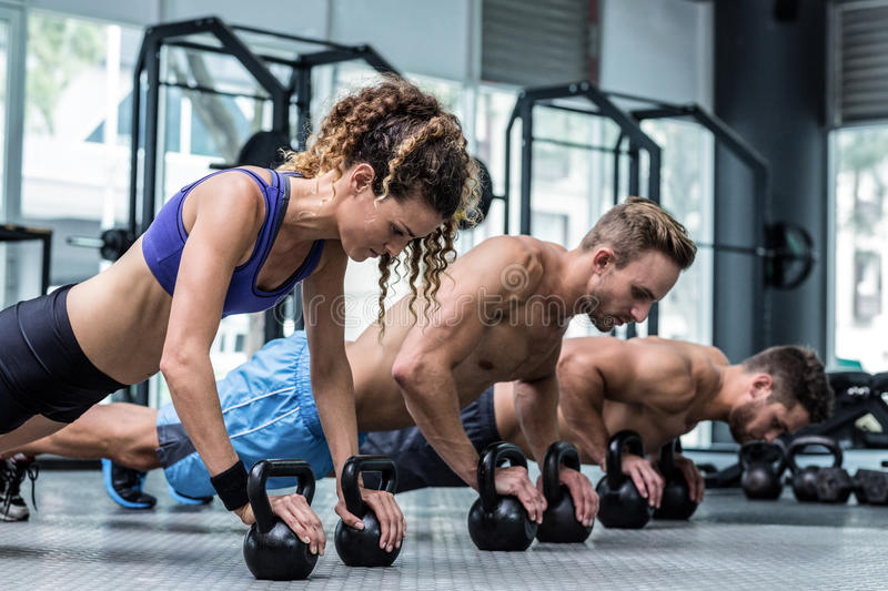 Three muscular athletes on a plank position. With kettlebells stock photography