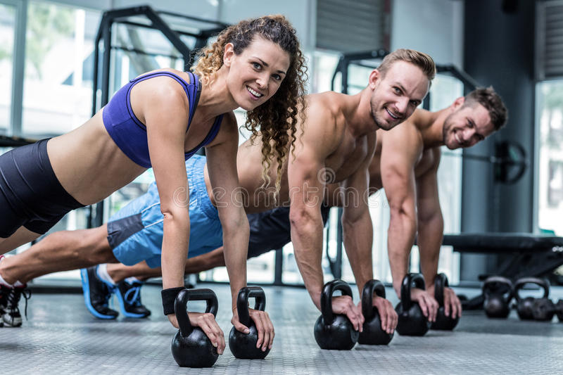 Three muscular athletes on a plank position royalty free stock image