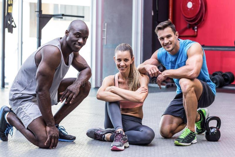 Three muscular athletes smiling at the camera stock photo