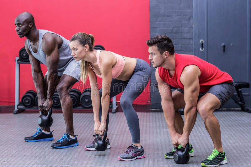Three muscular athletes squatting together royalty free stock images