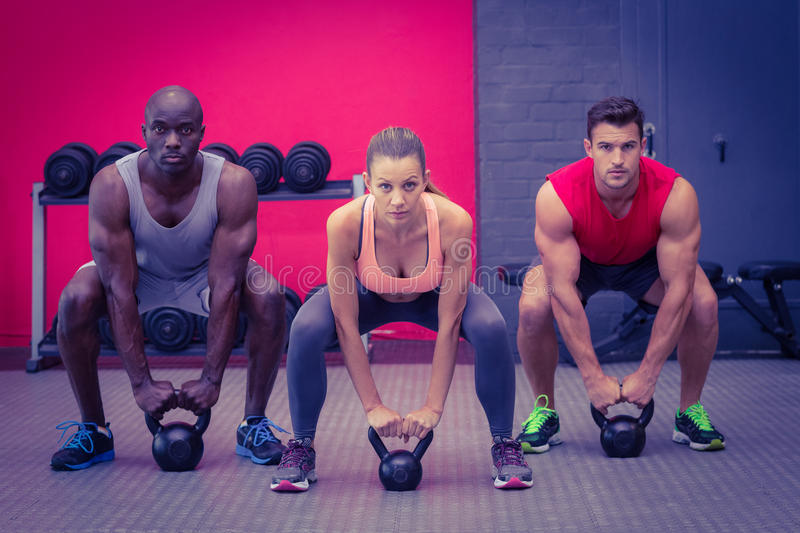 Three muscular athletes about to lift a kettle bell stock image