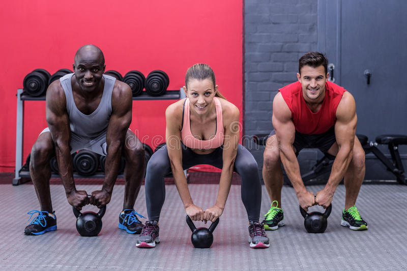 Three muscular athletes about to lift a kettle bell stock images