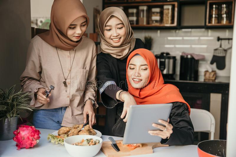 Learn new recipe online. Three muslim friend looking tablet and learn to make new food menu in the kitchen. cooking recipe royalty free stock photo