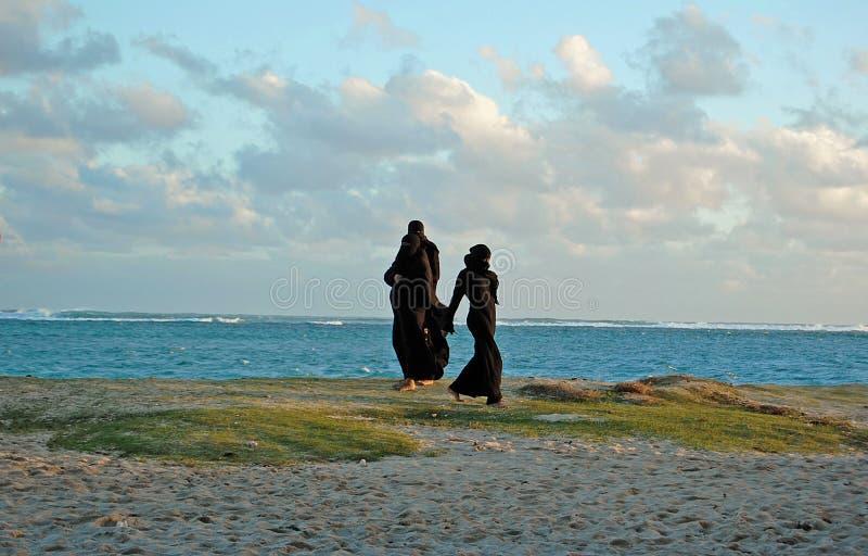 Three muslim women on the beach. Three muslim women wearing black niqab costumes on the beach at sunset royalty free stock photography