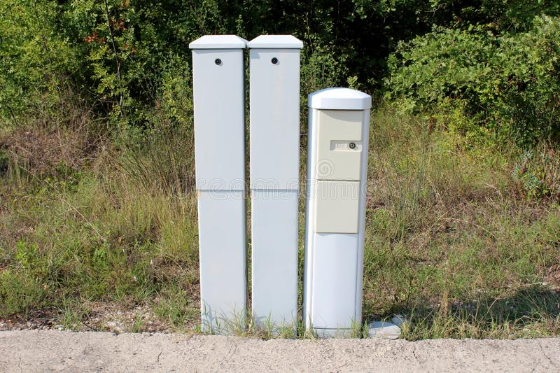 Three narrow tall plastic electrical boxes mounted on edge of asphalt backyard at abandoned industrial complex with tall grass and stock photography