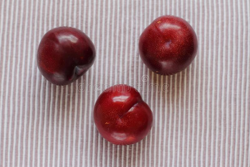 Three natural fresh plums on table stock images
