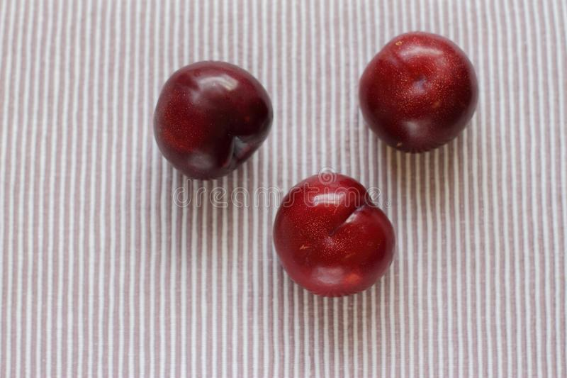 Three natural fresh plums on table royalty free stock image