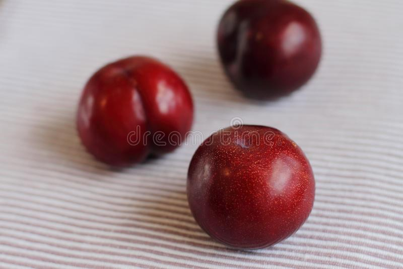 Three natural fresh plums on table royalty free stock images