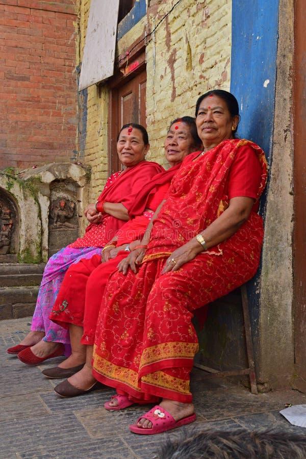 Three Nepalese ladies in red sarees sitting at Swayambhu Temple stock photos
