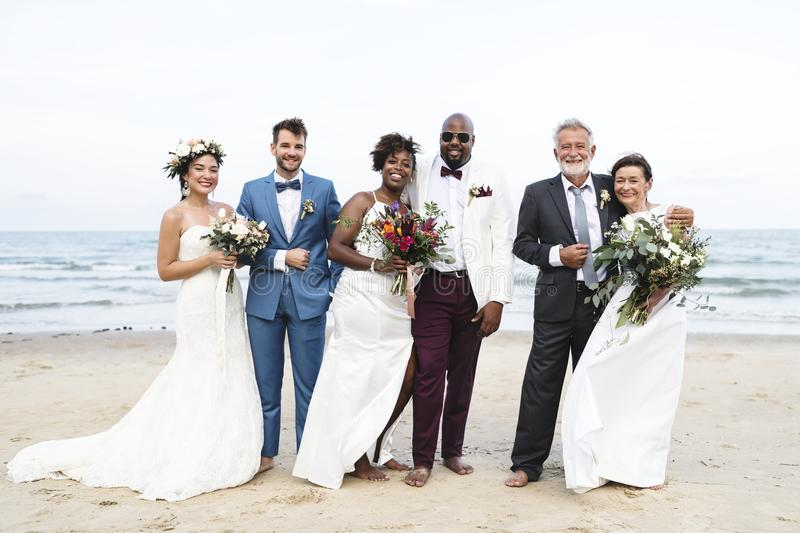 Three newly wed couples on the beach royalty free stock image
