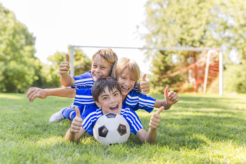 Three, Young boy with soccer ball on a sport uniform stock images