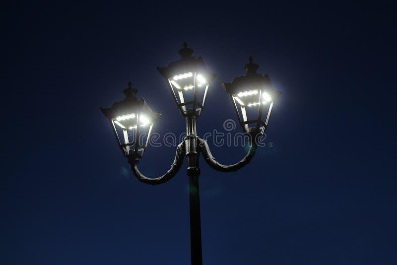 three night lights against the dark sky. Vintage led lights cast glare stock photos