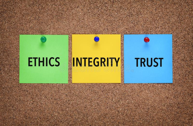 Three notes on corkboard with words Integrity, Trust, Ethics. Close-up stock image