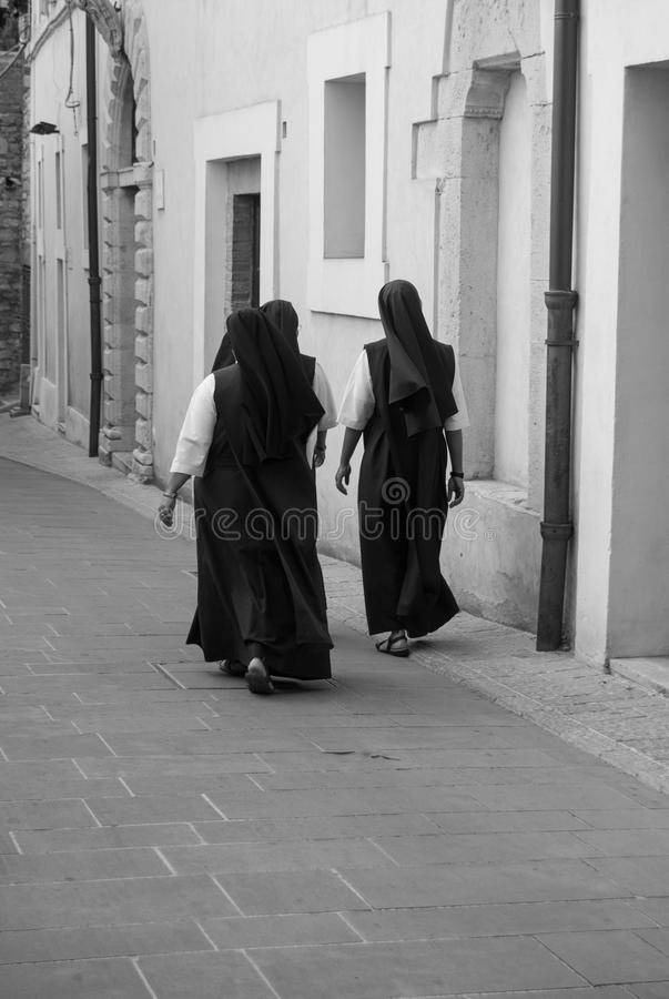 Three nuns of the Franciscan order. Three nuns of Franciscan order with sandals walking along a street in Assisi stock photography
