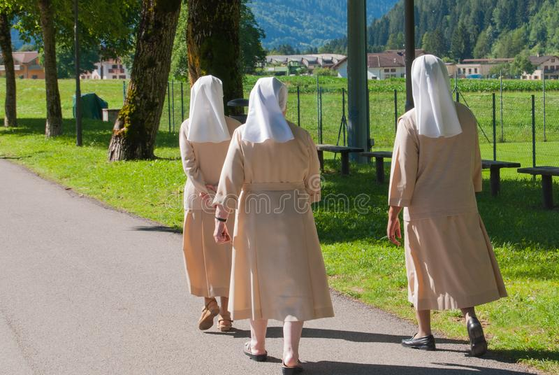 Three nuns walking on a asphalt road stock image