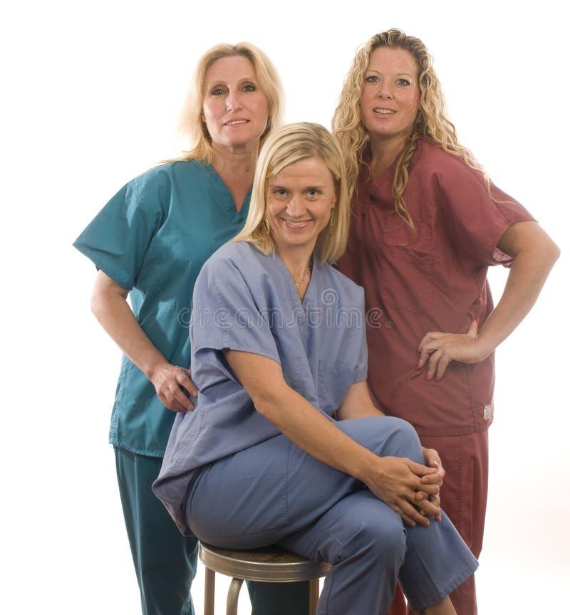 Three nurses in medical scrubs clothes stock photos